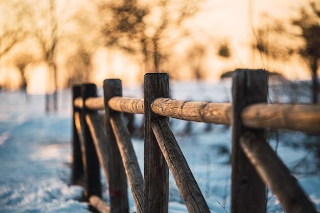 Cenário de inverno com corrimão de madeira perto de um caminho coberto de neve que atravessa um campo com árvores sem folhas no pôr do sol no campo