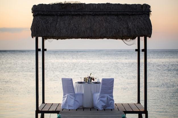 Cenário de jantar romântico na praia ao pôr do sol
