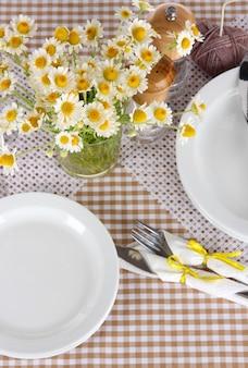 Cenário de mesa com camomilas em toalha de mesa quadriculada