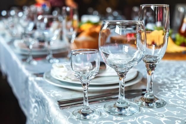 Cenário de mesa com copos, pratos, guardanapos e comida