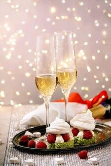 Cenário de mesa com duas taças de champanhe e sobremesas de merengue de baga na bandeja em pé na mesa de prata cintilante, corações brancos, luzes de bokeh