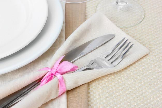 Cenário de mesa com garfo, faca, pratos e guardanapo