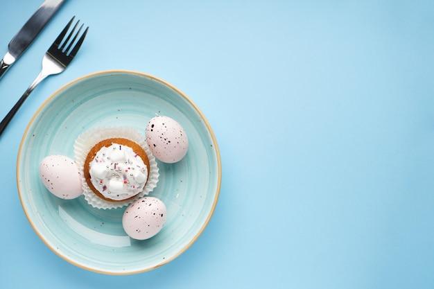 Cenário de mesa com talheres e enfeites de páscoa em azul