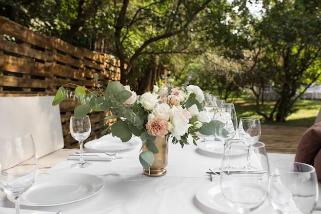 Cenário de mesa de casamento decorado com flores frescas em um vaso de latão