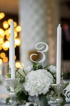 Cenário de mesa de casamento é decorado com flores frescas e velas brancas