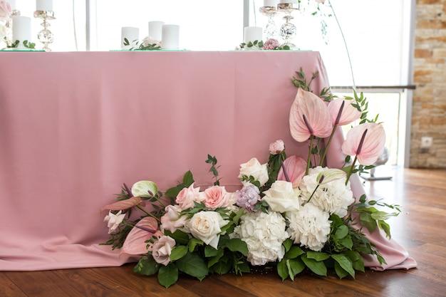 Cenário de mesa de casamento para os noivos é decorado com flores frescas