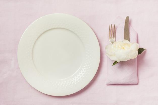 Cenário de mesa de elegância com planta na toalha de mesa de linho rosa