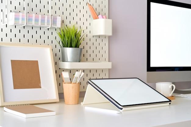 Cenário de mesa de escritório em casa com tablet de tela em branco de maquete e computador desktop. espaço de trabalho mínimo