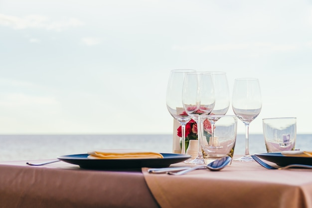 Cenário de mesa de jantar romântico com copo de vinho e outros