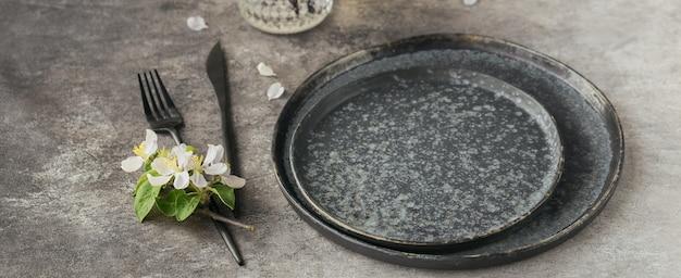 Cenário de mesa de mesa de primavera com ramos de macieira em flor e flores na mesa cinza