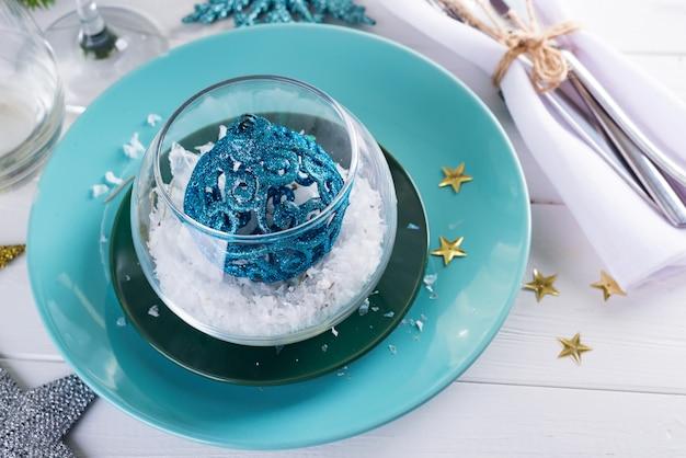 Cenário de mesa de natal com bola de brinquedo e decoração na mesa de madeira branca