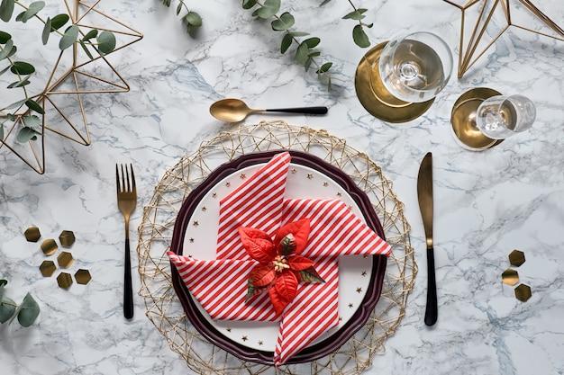 Cenário de mesa de natal com guardanapo vermelho, utensílios de ouro e folhas frescas de eucalipto em fundo de mármore branco