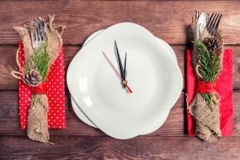 Cenário de mesa de Natal com placa, talheres e decorações