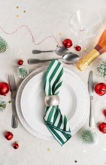 Cenário de mesa de natal com pratos brancos, talheres, guardanapo e com decoração de natal