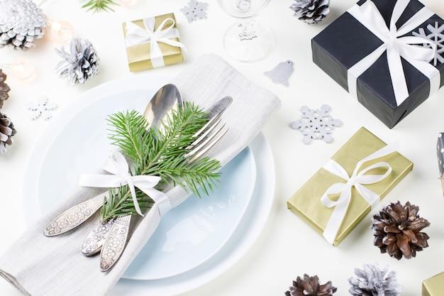 Cenário de mesa de natal com pratos, talheres, presentes e enfeites. vista do topo