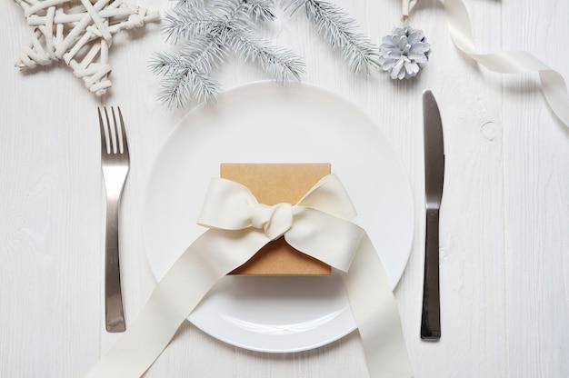 Cenário de mesa de natal com um presente vintage na mesa de madeira branca