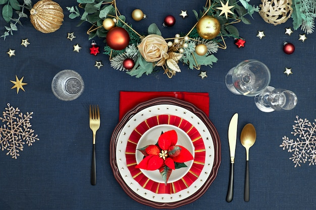 Cenário de mesa de natal nas cores azuis douradas, bordô e clássicas. vista superior no layout da mesa decorativa, talheres de ouro, pratos brancos com estrelas. decoração de natal tradicional em linho azul clássico