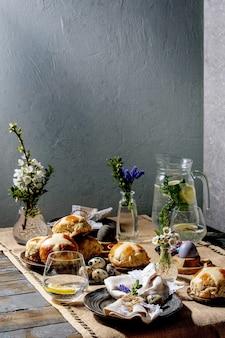 Cenário de mesa de páscoa com ovos coloridos e de chocolate, pãezinhos quentes e flores