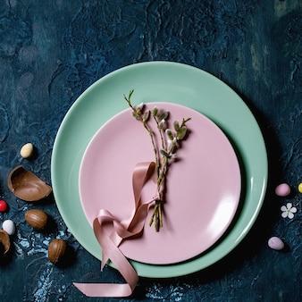Cenário de mesa de páscoa com ovos de chocolate, balas e pratos vazios