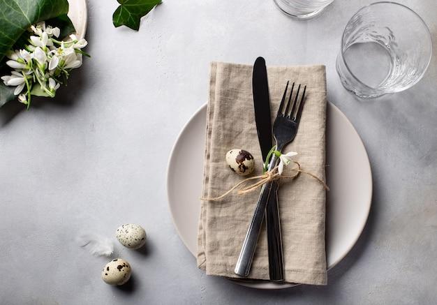 Cenário de mesa de páscoa decorado com ovos de codorna e flores da primavera. cores neutras naturais. imagem horizontal