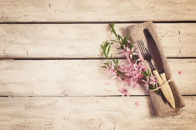 Cenário de mesa de primavera com flores de amêndoa e talheres