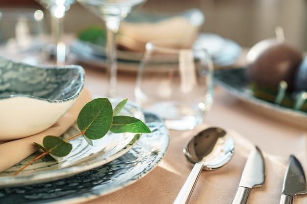 Cenário de mesa elegante bonita com louça elegante verde e talheres de prata