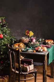 Cenário de mesa elegante para o jantar de natal em família com a árvore de natal no fundo e presentes na ...