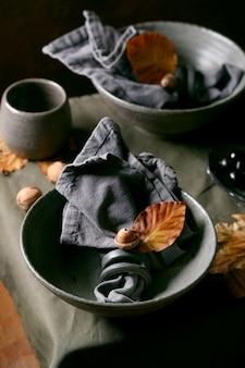 Cenário de mesa escuro de outono halloween ou ação de graças com talheres de cerâmica artesanais vazios, tigelas ásperas cinzas e copos na toalha de mesa de linho com bolotas e folhas amarelas de outono. fundo escuro