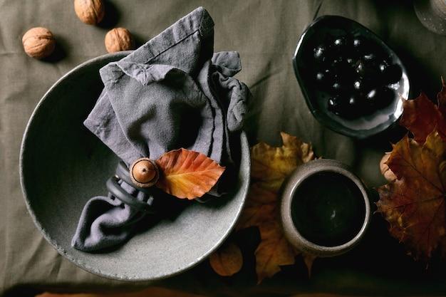 Cenário de mesa escuro de outono halloween ou ação de graças com talheres de cerâmica artesanais vazios, tigelas ásperas cinzas e copos na toalha de mesa de linho com bolotas e folhas amarelas de outono. postura plana