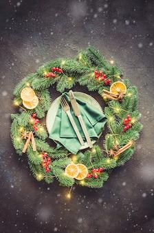 Cenário de mesa festiva com enfeites de natal em forma de uma guirlanda de natal
