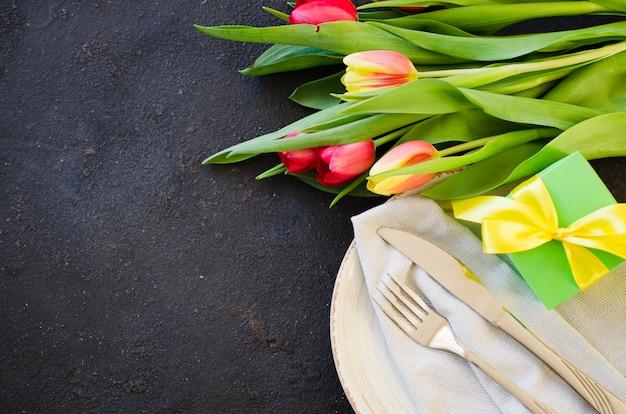 Cenário de mesa festiva com tulipas para aniversário, dia das mães ou para outro feriado.