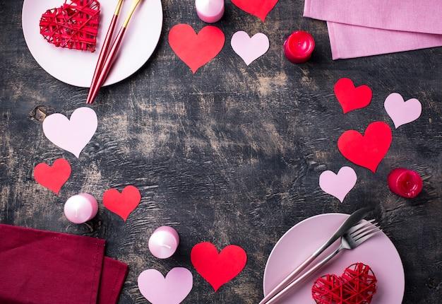 Cenário de mesa festiva de dia dos namorados com fundo de quadro de corações de papel