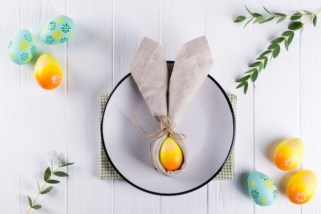 Cenário de mesa festiva de páscoa primavera com guardanapo de linho de orelhas de coelho e talheres de cozinha. vista plana leiga, superior.