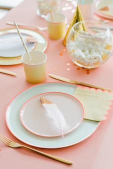 Cenário de mesa festiva decorativa para crianças festa jantar com toalha de mesa textilepink, placas coloridas de papel. feliz aniversário para decoração de chá de bebê ou menina