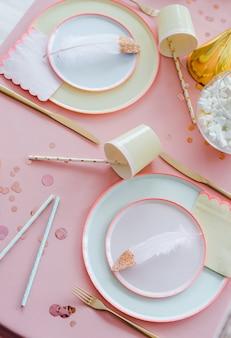 Cenário de mesa festiva para crianças festa jantar com toalha de mesa têxtil rosa, copos coloridos de papel, canudos de cocktail. feliz aniversário para menina, decoração de chá de bebê.