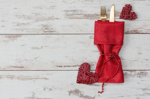 Cenário de mesa festiva para dia dos namorados com garfo e faca de ouro e decorações.