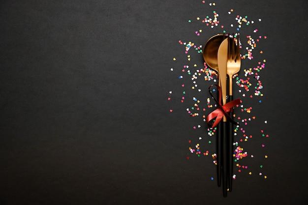 Cenário de mesa festiva para dia dos namorados com garfo, faca e corações em uma mesa preta com confete. espaço para texto.