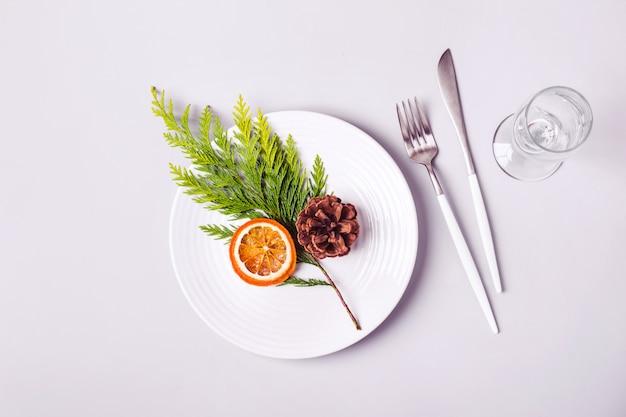 Cenário de mesa minimalista de natal com prato e talheres