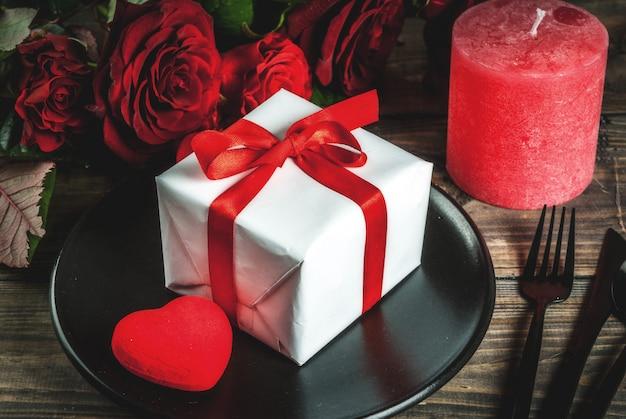 Cenário de mesa para dia dos namorados. buquê de rosas vermelhas, amarre com uma fita vermelha, caixa de presente, corações vermelhos, vela, prato, garfo, colher e faca. em uma mesa de madeira