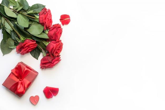 Cenário de mesa romântica com buquê de rosas vermelhas e presente. vista de cima. dia dos namorados.