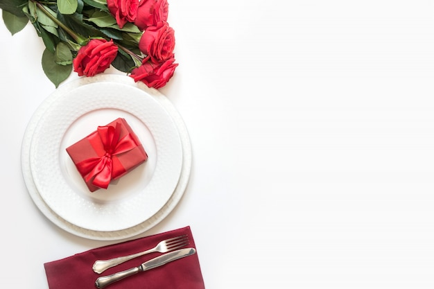 Cenário de mesa romântica com buquê de rosas vermelhas e presente.