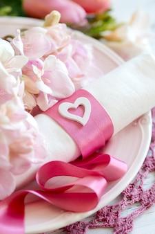 Cenário de mesa romântica com flores e fita rosa close-up