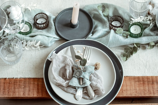 Cenário de mesa romântico com velas acesas e flores secas com muitos detalhes decorativos.