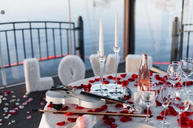 Cenário de mesa romântico dos namorados com vinho, pratos, copos vazios, pétalas de rosa, velas, violino