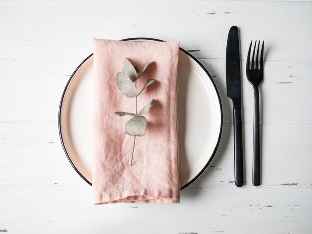 Cenário de mesa rústica com prato, guardanapo rosa, eucalipto e aparelhos na mesa de madeira branca. vista do topo.