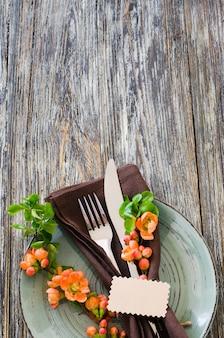 Cenário de mesa vintage com flores delicadas e etiqueta na mesa gasto rústica.