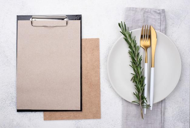 Cenário de mesa vista superior com prancheta e legumes