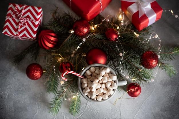 Cenário de natal com chocolate quente em uma caneca de suéter chique com marshmallows, bastões de doces, cervos de madeira e luzes de natal no fundo