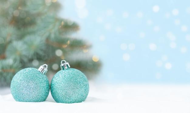 Cenário de natal com enfeites de natal na neve em frente à árvore de natal