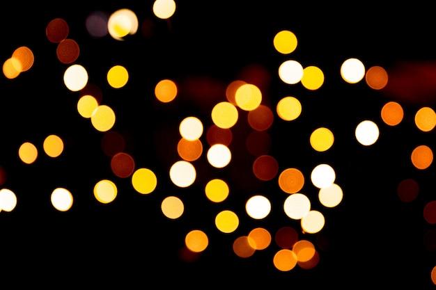 Cenário de ouro brilhante de férias. desfocado e turva muitos redondo luz amarela sobre fundo preto de natal